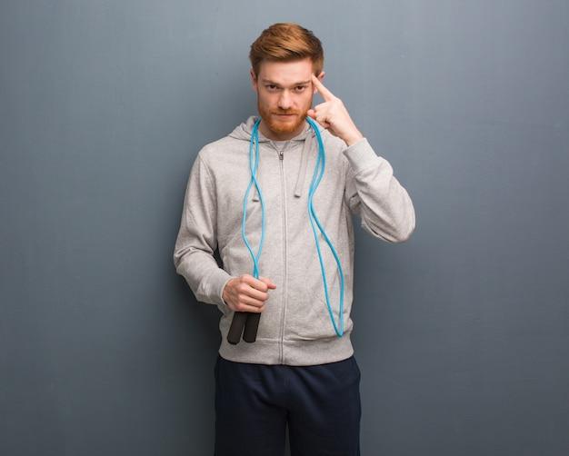 Junger rothaarigeignungsmann, der an eine idee denkt. er hält ein springseil. Premium Fotos