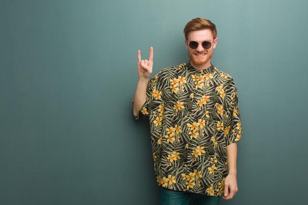 Junger rothaarigemann, der die exotische sommerkleidung tut eine felsengeste trägt Premium Fotos