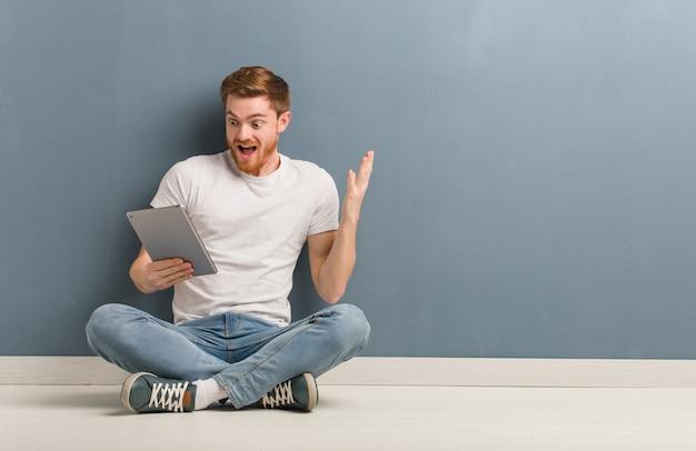 Junger rothaarigestudentenmann, der auf dem boden feiert einen sieg oder einen erfolg sitzt. er hält eine tablette in der hand. Premium Fotos