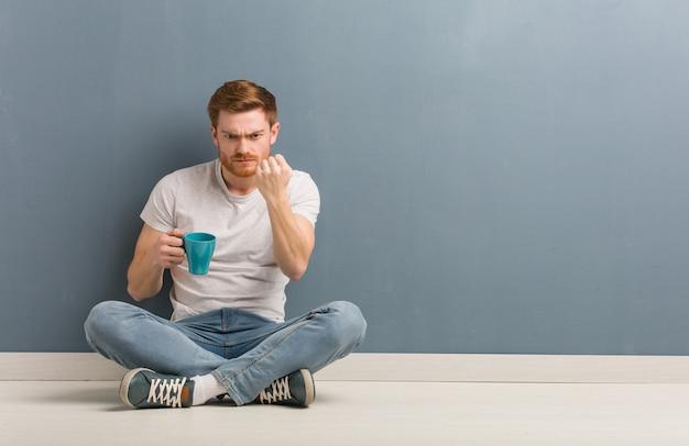 Junger rothaarigestudentenmann, der auf dem boden zeigt faust zur front, verärgerter ausdruck sitzt. er hält eine kaffeetasse in der hand. Premium Fotos