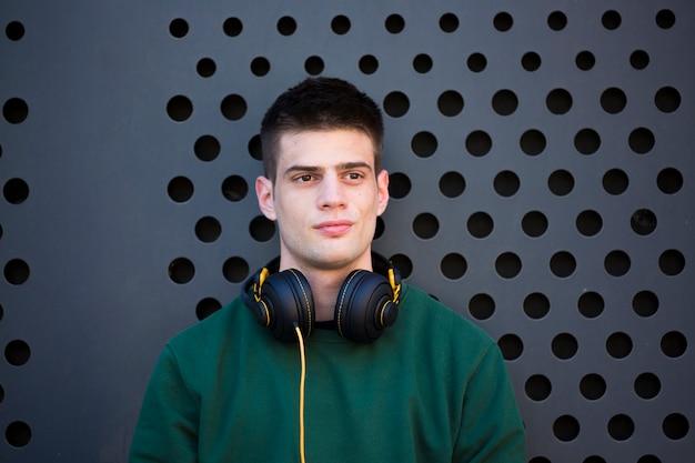 Junger ruhiger mann mit den kopfhörern, die weg schauen Kostenlose Fotos