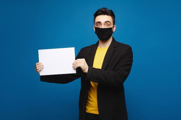 Junger schockierter mann in einer schwarzen schutzmaske, die ein leeres blatt papier hält und in die kamera schaut, lokalisiert auf den blauen hintergrund. werbekonzept. gesundheitskonzept Premium Fotos
