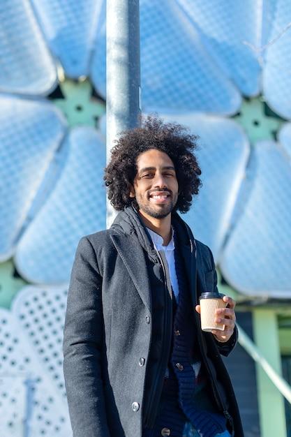 Junger schöner afroamerikanermann, der glücklich lächelt. stehend mit einem lächeln im gesicht, das eine tasse kaffee zum mitnehmen in der stadtstraße trinkt. Premium Fotos
