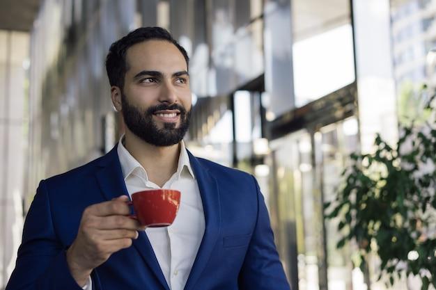 Junger schöner geschäftsmann, der kaffee im café trinkt Premium Fotos