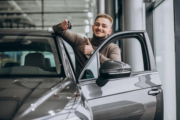 Junger schöner mann, der ein auto in einem autoausstellungsraum wählt Kostenlose Fotos