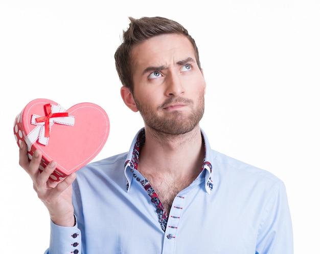 Junger schöner mann, der ein geschenk hält und denkt - lokalisiert auf weiß. Kostenlose Fotos