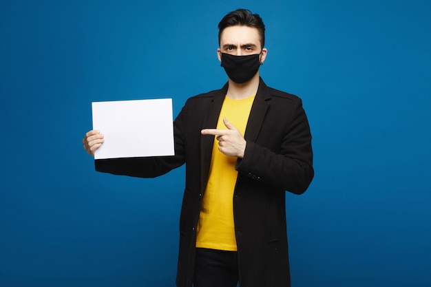 Junger schöner mann, der leeres blatt papier hält, lokalisiert am blauen hintergrund. junger mann, der auf ein blatt des papierblatts zeigt und in die kamera schaut. werbekonzept Premium Fotos