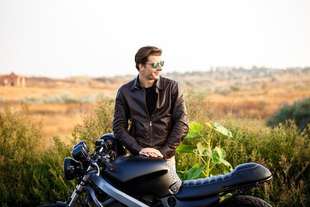 Junger schöner mann, der nahe seinem motorrad an der landstraße aufwirft. Kostenlose Fotos