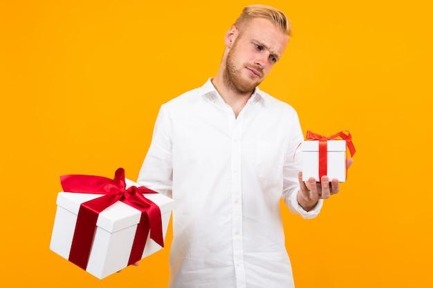 Junger schöner mann hält zwei weiße kisten mit geschenken und wählt isoliert auf gelb Premium Fotos