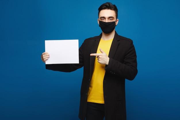 Junger schöner mann in der schwarzen schutzmaske, die leeres blatt papier hält und darauf zeigt, lokalisiert am blauen hintergrund. werbekonzept. gesundheitskonzept Premium Fotos