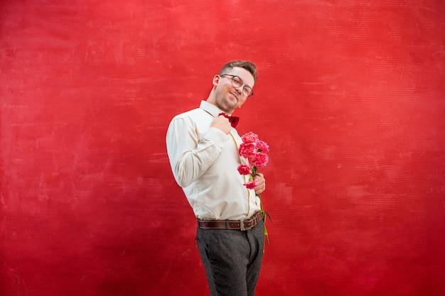 Junger schöner mann mit blumen auf rotem studiohintergrund Kostenlose Fotos