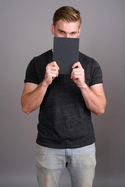 Junger schöner mann mit dem blonden haar, das graues hemd auf grauer wand trägt Premium Fotos