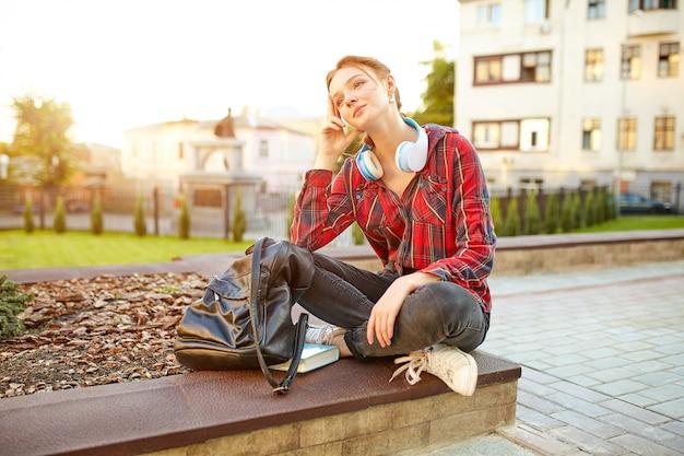 Junger schöner student, der kopfhörer eines karierten hemdes und einen rucksack stillstehen auf der straße trägt Premium Fotos