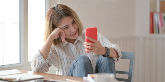 Junger schöner weiblicher designer, der smartphone betrachtet und auf dem stuhl sitzt Premium Fotos