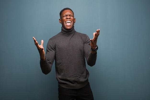 Junger schwarzer afroamerikanermann, der wütend schreit, sich gestresst und genervt mit den händen in der luft fühlt und sagt, warum ich gegen die schmutzwand Premium Fotos