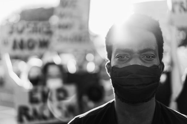 Junger schwarzer mann, der gesichtsmaske während des protestes der gleichberechtigung trägt Premium Fotos