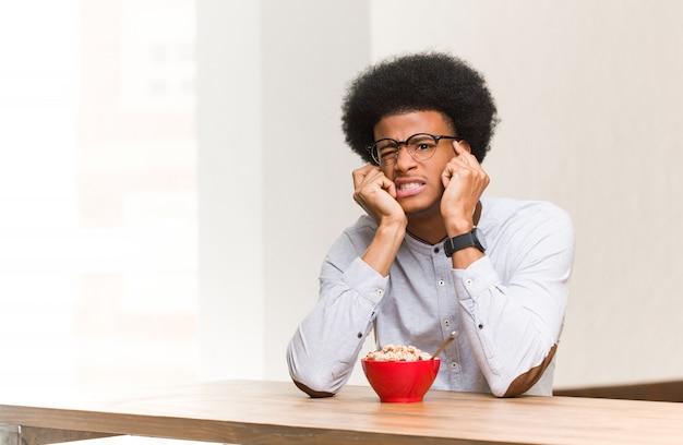 Junger schwarzer mann, der hoffnungslos und traurig frühstückt Premium Fotos