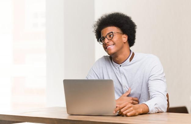 Junger schwarzer mann, der seinen laptop träumt vom erreichen von zielen und von zwecken verwendet Premium Fotos