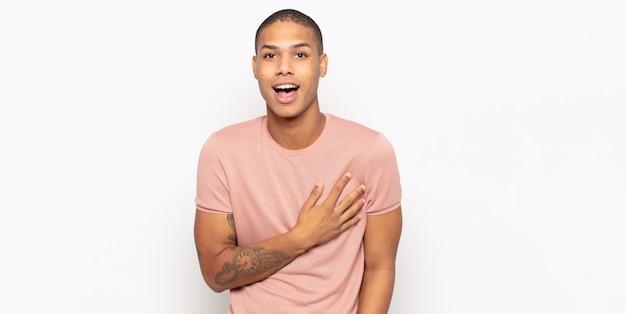 Junger schwarzer mann, der sich schockiert und überrascht fühlt, lächelt, hand zu herzen nimmt, glücklich ist, derjenige zu sein oder dankbarkeit zu zeigen Premium Fotos