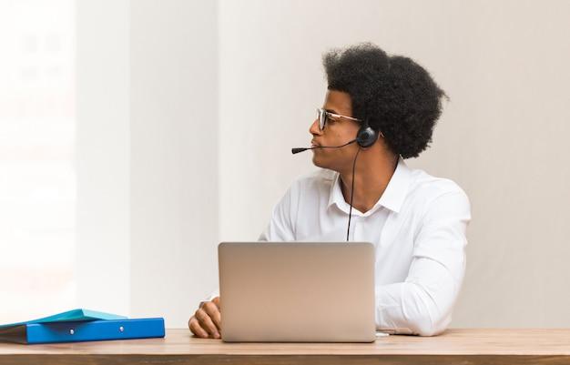 Junger schwarzer mann des telemarketers auf der seite, die nach vorne schaut Premium Fotos
