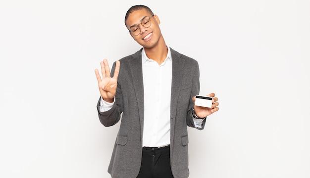 Junger schwarzer mann lächelt und sieht freundlich aus, zeigt nummer vier oder vierten mit der hand nach vorne, countdown Premium Fotos