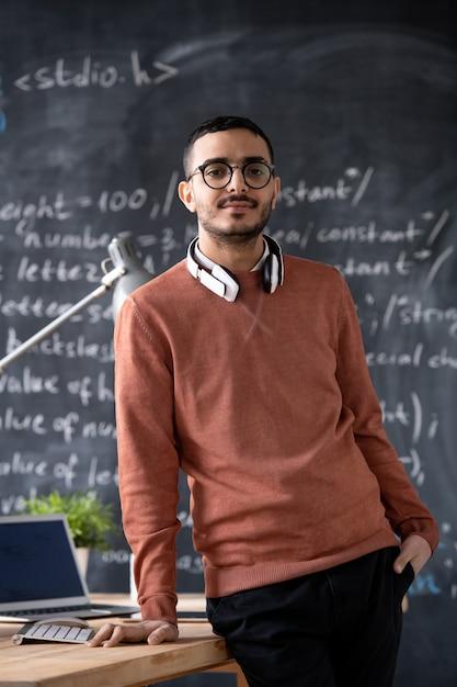 Junger selbstbewusster it-manager in freizeitkleidung und brillen, der vom schreibtisch mit laptop über tafel mit formel steht Premium Fotos