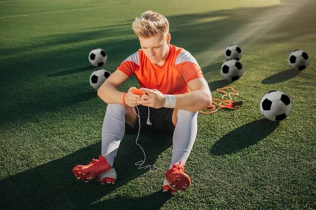 Junger spieler sitzt allein auf grünem rasen Premium Fotos