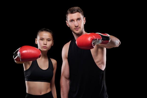 Junger sportler und sportlerin im training für aktivkleidung und boxhandschuhe Premium Fotos