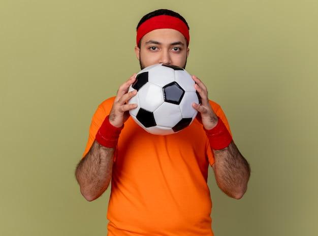 Junger sportlicher mann, der kamera betrachtet, die stirnband und armband hält, hält ball lokalisiert auf olivgrün Kostenlose Fotos