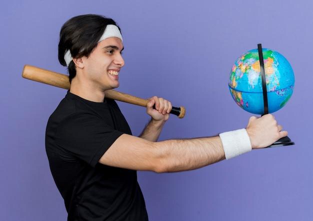 Junger sportlicher mann, der sportbekleidung und stirnband hält baseballschläger und globus, die fröhlich lächeln Kostenlose Fotos