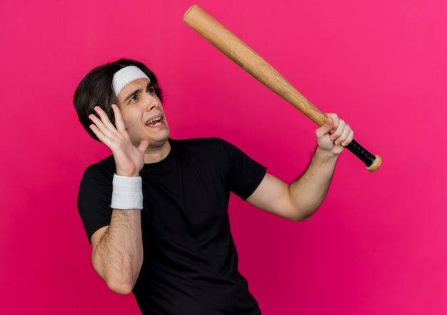 Junger sportlicher mann, der sportbekleidung und stirnband hält, die baseballschläger betrachten, der etwas verängstigt macht, das verteidigungsgeste mit hand macht Kostenlose Fotos