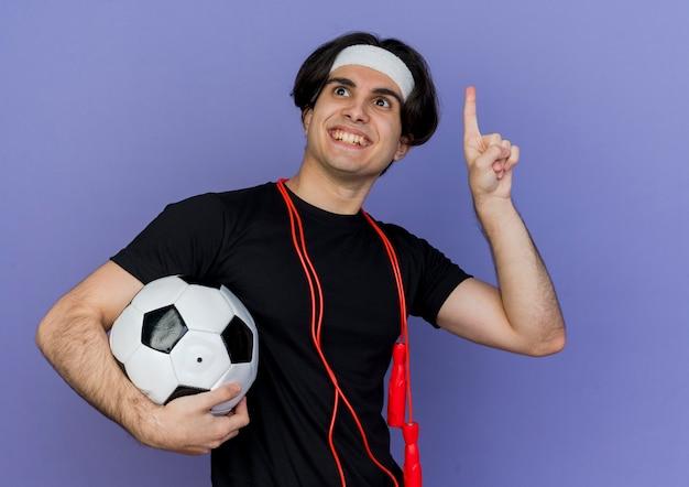 Junger sportlicher mann, der sportbekleidung und stirnband mit springseil um den hals hält, der fußball pointign up mit finger lächeln, der neue idee hat Kostenlose Fotos