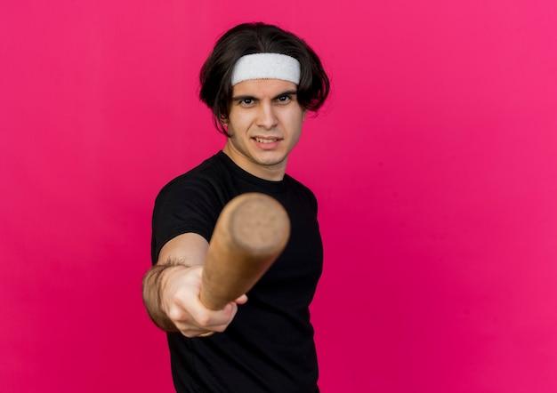 Junger sportlicher mann, der sportbekleidung und stirnband trägt, die mit baseballschläger auf kamera mit ernstem gesicht zeigen Kostenlose Fotos