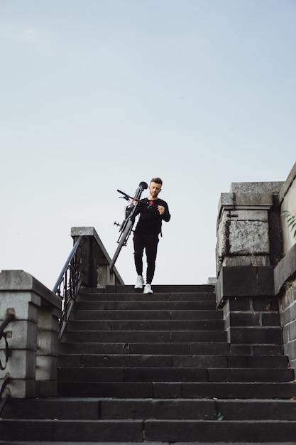 Junger sportmann auf einem fahrrad in einer europäischen stadt. sport in urbanen umgebungen. Kostenlose Fotos