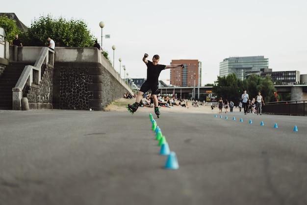 Junger sportmann auf rollschuhen in einer europäischen stadt. sport in urbanen umgebungen. Kostenlose Fotos