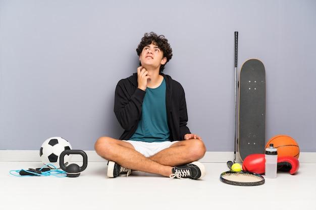 Junger sportmann, der auf dem boden um viele sportelemente denkt eine idee sitzt Premium Fotos