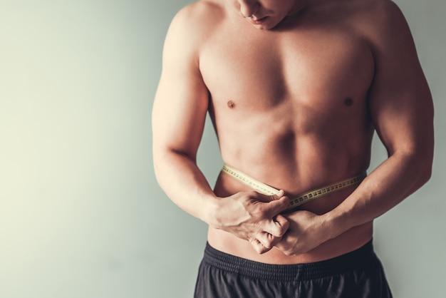 Junger sportmann, der seine taille misst. Premium Fotos