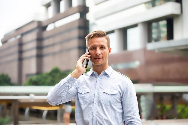 Junger städtischer berufsmann, der intelligentes telefon verwendet. geschäftsmann, der intelligentes mobiltelefon hält Premium Fotos