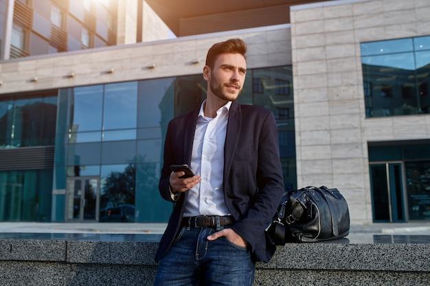 Junger städtischer berufsmann, der intelligentes telefon verwendet. geschäftsmann, der mobilen smartphone unter verwendung der tragenden jacke sms-mitteilung der app simst Premium Fotos
