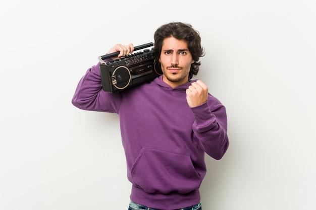 Junger städtischer mann, der einen guettoblaster zeigt faust zur kamera, aggressiver gesichtsausdruck hält. Premium Fotos