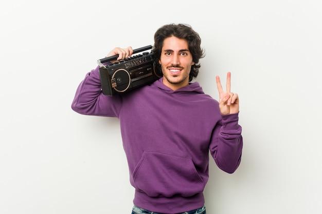 Junger städtischer mann, der einen guettoblaster zeigt nummer zwei mit den fingern hält. Premium Fotos