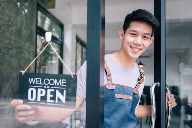 Junger startkaffeecafébesitzer öffnen und begrüßen kunden. Premium Fotos