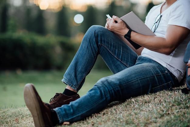 Junger stattlicher mann, der auf grünem gras sich entspannt Kostenlose Fotos