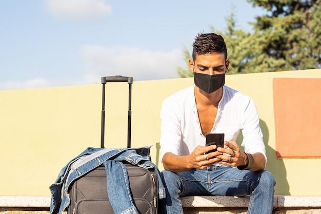Junger stilvoller kaukasischer mannreisender mit einer schwarzen covid-schutzmaske unter verwendung des smartphones Premium Fotos