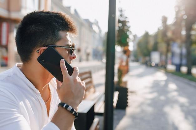 Junger stilvoller kerl im hemd mit telefon auf bank am sonnigen tag draußen Kostenlose Fotos
