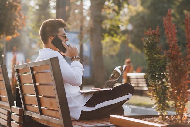 Junger stilvoller kerl im hemd mit telefon und notizbuch auf bank am sonnigen warmen tag draußen, freiberuflich tätig Kostenlose Fotos