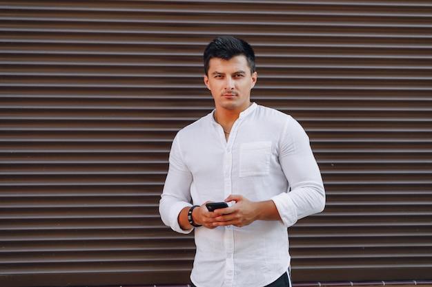 Junger stilvoller kerl im hemd schreibend am telefon Kostenlose Fotos