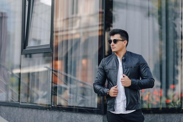 Junger stilvoller kerl in den gläsern in der schwarzen lederjacke auf glasoberfläche Kostenlose Fotos