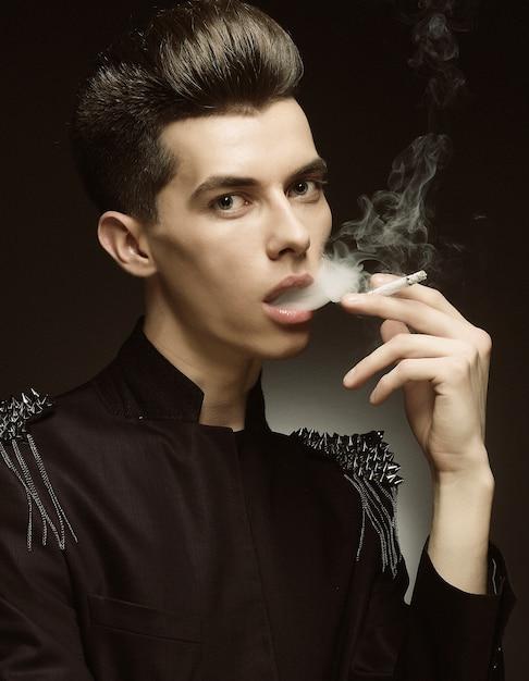Junger stilvoller mann, der eine zigarette raucht Premium Fotos