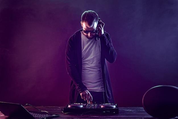 Junger stilvoller mann in den gläsern, die hinter mischender konsole auf farbigem rauchstudio aufwerfen Premium Fotos